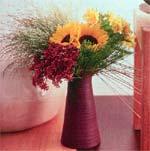 En kontrastfylld höstbukett med kraftiga solrosor, eleganta gräs, knippen av Sedum och kraftigt gul Alstroemeria arrangerade på olika nivåer.
