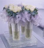 Fyra vaser med gräddfärgad rosor Akito i ett näste av blad från Eucalyptus Cinerea.