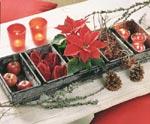 Fynda på loppmarknader, i källare och i vindsutrymmen. Här har gamla bakformar fyllts med klart röda julstjärnor och färgglada dekorationer som rödkindade äpplen, små påsar i sammet, nypon och ljus.