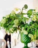 Ett pampigt arrangemang med olvon, liljor, rams och lotus i skön grön vas.