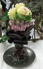 Hög glasvas med upprullade vinröda blad, små lila rosor och limegröna/rosa